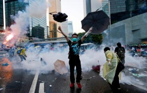 A protester raises his umbrellas in front of tear gas which was fired by riot police to disperse protesters blocking the main street to the financial Central district outside the government headquarters in Hong Kong